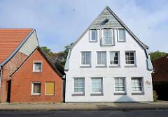 Historisches Wohnhaus mit Dachwinde und zur Wohnung umgebautem Dachspeicher - lks. kleines einfaches Wohngebäude mit roter Ziegelfassade - Architektur in Otterndorf.