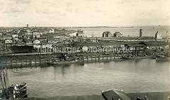 Alte Luftaufnahme vom Landwehrkanal / Hafen Cuxhaven. Frachter liegen am Kai, Lagerschuppen - im Hintergrund die Deichpromenade und die Kugelbarke.