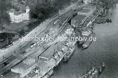 Alte Luftaufnahme von der Hafenbahn und Hafenanlage beim Altonaer Hafen an der Großen Elbstraße. Eisenbahnwaggons stehen auf der Gleisanlage beim Altonaer Kaispeicher - auf der gegenüberliegenden Seite der Donnerpark und das Donnerschloss.