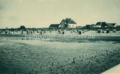 Nordseestrand mit Strandkörben und Ferienhäuser am Deich beim Nordseebad Duhnen.