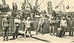 Verladung von Wollballen in Antwerpen / Belgien - Hafenarbeiter auf dem Kai und an Deck des Frachtschiffs.