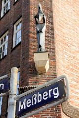 Straßenschild Meßberg - im Hintergrund eine der Figuren am Messberghof im Hamburger Kontorhausviertel.