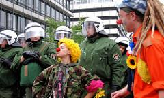 Clandestine Insurgent Rebel Clown Army / CIRCA; Heimliche Aufständische Rebellen-Clownarmee: Clown Demonstranten bei der Arbeit - Polizisten schauen zu.