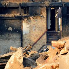 Blick ins ehem. Wohnzimmer mit Blumentapete / Rosentapete - Treppenaufgang, Fachwerkbalken. Abriss vom Bauernhof Ahlers im Dorfring von Wilstedt.