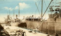 Alte colorierte Fotografie vom Hafen in Tunis / Tunesien - Dampfschiffe / Frachter; angelehnte Holzleitern - gestapelte Säcke auf dem Kai.