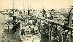 Historische Fotografie aus der Hafenstadt Rufisque im Senegal - Segelschiffe am Holzkai - gestapelte Säcke.