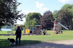 Kinderspielplatz mit Spielgeräten - im Hintergrund der Öjendorfer See in Hamburg Billstedt.