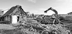 Abriss vom Bauernhof Ahlers im Dorfring von Wilstedt / Ortsteil in Tangstedt. Reste vom reetgedeckten Wohnhaus - Bauschutt, Bagger beim Sortieren in Container.