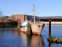 Altes rostiges Schiff im Moldauhafen Hamburg Kleiner Grasbrook - im Hintergrund das Lagerhaus D und das Übersee-Zentrum. Das Hafenbecken Moldauhafen wurde  1887 gebaut - ein 30.000 Quadratmeter großes Gelände wurde aufgrund des nach dem Ersten We