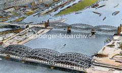 Historisches Flugbild von den Norderelbbrücken in Hamburg. Im Vordergrund die Freihafenelbbrücke, dahinter die Elbbrücke mit den hohen Portalen, die die Veddel und Hamburg Rothenburgsort verbinden.