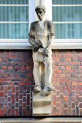 Sandsteinskulptur - Beruf Steinmetz / Maurer; männliche Figur mit Schürze, Hammer und Stein;  Bildhauer Richard Kuöhl -  Altstädter Hof, Kontorhausviertel Hamburg.