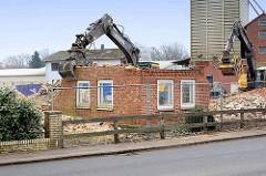 Abriss vom Wohngebäude des Bauernhofs Ahlers in Tangstedt. Der Greifer des Baggers bricht Teile aus der Hauswand.