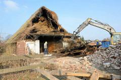 Abriss vom Bauernhof Ahlers im Dorfring von Wilstedt / Ortsteil in Tangstedt. Der Bagger sortiert Holzteile für den Abtransport / Recycling auf einen Haufen.