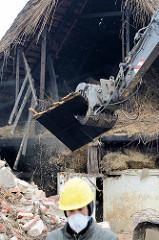 Rückbau vom historischen Reetdachhaus in Wilstedt - Abrissbagger bei der Arbeit, Teile der Holzdecke im Greifer.