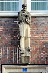 Sandsteinskulptur - Beruf Architekt - männliche Figur mit Zirkel und Haus in der Hand haltend; Bildhauer Richard Kuöhl - Altstädter Hof, Kontorhausviertel Hamburg.