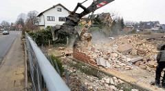 Das Gebäude ist abgerissen - Reste des Mauerwerkes / Schutts werden vom Greifbagger zusammengetragen.
