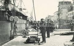 Historische Hafenszene aus Antwerpen / Belgien - Hafenarbeiter entladen ein Frachtschiff - Fässer am Ladegeschirr, Wohnhäuser im Hintergrund.