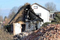 Reste vom Wohnhaus mit Reetdach - im Vordergrund Berg von Schutt; Abriss vom Bauernhof Ahlers im Dorfring von Wilstedt / Ortsteil in Tangstedt.