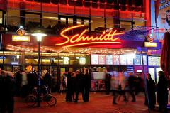 Schmidt Theater an der Reeperbahn / Spielbudenplatz - beleuchteter Schriftzug, TheaterbesucherInnen warten auf der Straße - Nachtaufnahme.