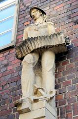 Sandsteinskulptur - Beruf Matrose / Seefahrer- männliche Figur mit Akkordeon zu den Füssen ein Anker; Bildhauer Richard Kuöhl - Altstädter Hof, Kontorhausviertel Hamburg.