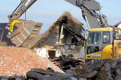 Backenbrecherlöffel im Einsatz beim Abbruch vom  Bauernhof. Der Bagger zerkleinert Bauschutt und Abbruchmaterialien.