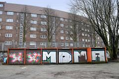Mit Graffiti versehene  Garagentore an der Tunnelstraße, dahinter der ehem. Zollzaun und Wohnhäuser an der Straße Passierzettel.