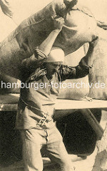 Historische Fotografie - ein Hafenarbeiter in Antwerpen / Belgien lädt sich einen Sack auf die Schulter.