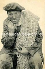 Altes Portrait eines Fischers mit Baskenmütze und Fischernetz über der Schulter / Frankreich.