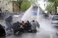Die friedliche Straßenblockade durch Demonstranten wird von der Hamburger Polizei durch den Einsatz eines Wasserwerfers aufgelöst.