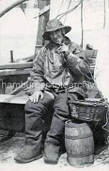 Historische Fotografie eines Fischers in Ölzeug mit Gummistiefeln; Pfeife rauchend - Holzfass und Weidenkorb / Frankreich.