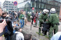 Demonstration in Hamburg - Ludwig Erhard Straße; zwei Polizisten nehmen einen Demonstranten fest; er wird über einen Parkpoller gedrückt - Fotografen bei der Arbeit.