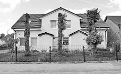 Symmetrisches Doppelhaus mit zugemauerten Eingängen - gestutze Linden im Vorgarten.