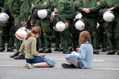 Ruhe vor dem Sturm - Mädchen sitzen auf der Straße, die Polizeimanschaften sammeln sich. Demonstation am Millerntor in Hamburg St. Pauli.