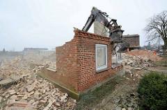 Noch steht die Hausecke vom Gebäude - der Greifer des Baggers bricht Teile des Mauerwerks aus der Mauer.
