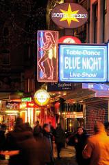 Nachtleben in Hamburg - Kiez bei Nacht; Schilder für Table Dance und Paradise Sex auf der Reeperbahn - Langszeitaufnahme, Personen in Bewegung.