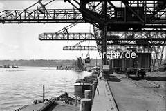 a Kohleverladebrücken im Hamburger Kohlehafen - Schuten liegen am Kai, auf dem Kai Güterwaggons.