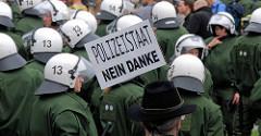 Polizeimannschaft in Kampfmontur mit Helm - Hutträger mit Schild Polizeistaat Nein Danke; Demonstration in Hamburg.