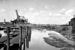 a Abgeböschtes Ufer vom Kohlehafen im Hamburger Hafen - Schuten mit Kohle beladen leigen an Dalben - im Hintergrund Kohleverladebrücken.