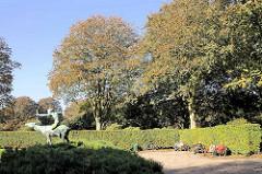 Herbstnachmittag im Hamburger Stadtpark - ParkbesucherInnen sitzen auf Bänken in der Sonne - Skulptur  Diana + Hirschkuh.