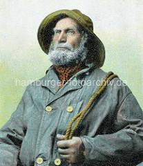 Colorierte historisch Aufnahme eines Fischers mit dichtem Bart in Ölzeug, ein Tau haltend.