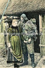 Fischerin und Fischer mit Netz und Ölzeug vor einer reetgedeckten Kate / Holztür; Ostsee - Deutschland.