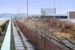 Hochwasserschutz / Sturmflutschutz am Holthusenkai im Hamburger Stadtteil Kleiner Grasbrook - Spundwand; dahinter Gleisanlagen der Hamburger Hafenbahn und das Übersee-Zentrum und die Freihafenelbbrücken.