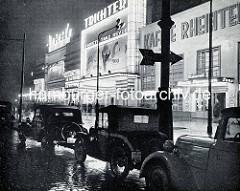 Historische Nachtaufnahme von der Reeperbahn in Hamburg St. Pauli - alte Autos stehen am Strassenrand, beleuchtete Fassade vom Kaffee Rheinterrassen.