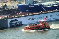 Blick über die Elbe zum Trockendock / Schwimmdock der Werft Blohm + Voss - das Frachtschiff Bulknes ist eingedockt, eine Hafenfähre fährt Richtung Landungsbrücken.