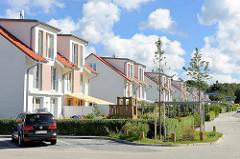 Neubaugebiet in Hamburg Billstedt - moderne Doppelhäuser mit kleinem Vorgarten in der Hans-Rubbert-Straße - junge Straßenbäume mit Stützpfahl.