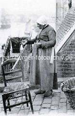 Alte Fischerin, repariert zum Trocknen aufgehängte Netze; kaputter Baststuhl - im Hintergrund Schiffe im Hafen / Frankreich.