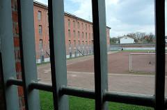 Vergittertes Gefängnisfenster - Blick auf den Sportplatz der Hamburger Justizvollzugsanstalt Fuhlsbüttel - Santa Fu.