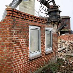 Noch steht die Hausecke vom Gebäude / Wohnzimmer - der Greifer des Baggers bricht Teile des Mauerwerks aus der Mauer.