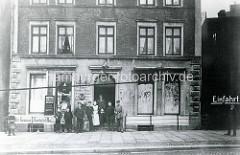 Historische Ansicht vom Sieldeich auf der Hamburger Veddel - Anwohner stehen im Hauseingang; Cigarren / Zigarettengeschäft.