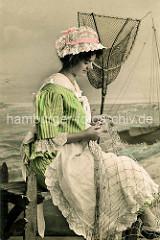 Historische Studioaufnahme - Fischerin mit weisser Schürze und rosa colorierter Spitzenhaube flickt ein Netz; Ketscher als Dekor - Hintergrundbild Wasser / Meer mit Ruderboot - Frankreich.